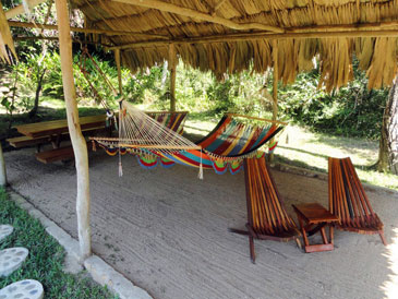 Palapa furnished with hammocks, picnic table and chairs